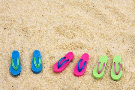 Colored Flip flops on sand – beach background photo
