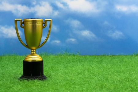 greatest: Trophy sitting on grass with copy space