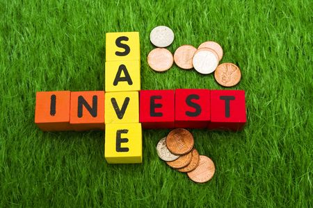 Alphabet blocks spelling save and invest with coins on grass Stock Photo - 2839936