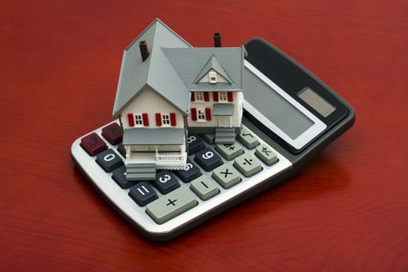 escrow: Model house sitting on a calculator � calculating payments