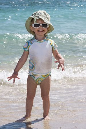 Very happy cute little toddler girl on the beach