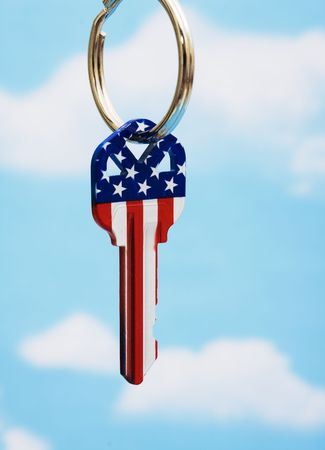 real estate investment: House key with American flag with a sky background Stock Photo