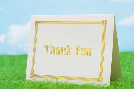 Thank you card on grass with sky background
