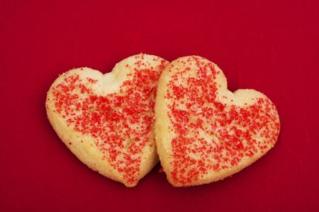 Two heart shaped cookies on a red background photo