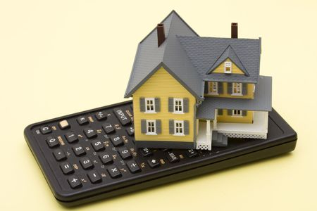 Model house sitting on calculator on a yellow background Stock Photo - 3260076