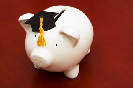 cost of education: Piggy bank with graduation cap – cost of education Stock Photo