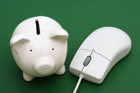 Piggy bank with computer mouse on a green background photo