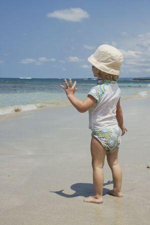 Toddler girl on the beach waving goodbye photo
