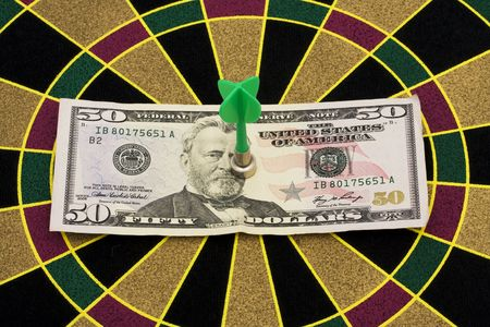 50 dollar bill: Magnetic dart board with darts � on target with your money Stock Photo