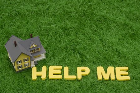 help me: House with the words help me on grass. mortgage crisis