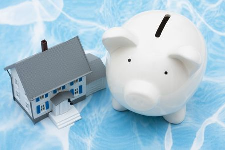 owe: Model house with piggy bank on blue background. home finances