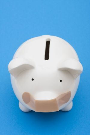 Piggy bank with adhesive bandage on mouth on blue background, investment trouble photo