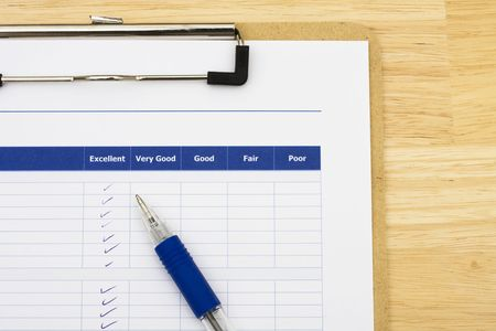 Survey attached to clipboard sitting on table with blue pen, excellent customer service Stock Photo - 3437996