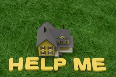 housing crisis: House with the words help me on grass. mortgage crisis