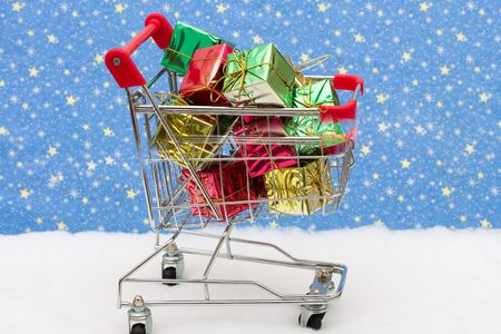 Shopping cart filled with presents on snow with star background, Christmas shopping photo