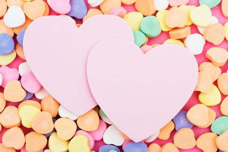 Candy hearts with two blank paper heart
