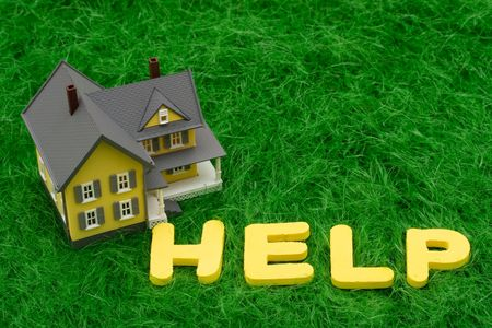 housing crisis: House with the word help on grass. mortgage crisis Stock Photo