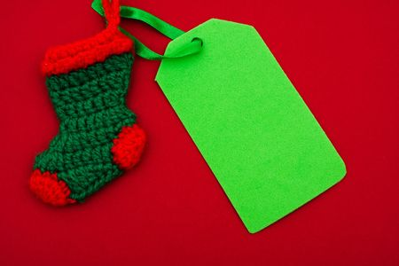 Christmas stocking with blank gift card on red background � Christmas stocking photo