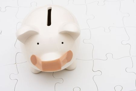 Piggy bank sitting on white puzzle, understanding personal finances