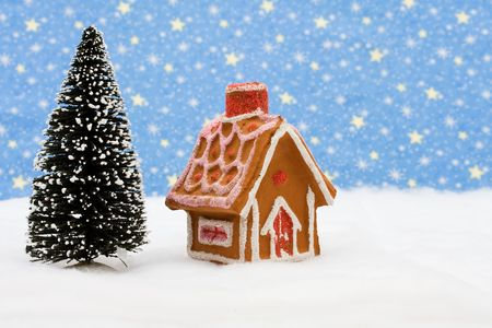 Gingerbread house and tree on snow with star background, gingerbread house photo