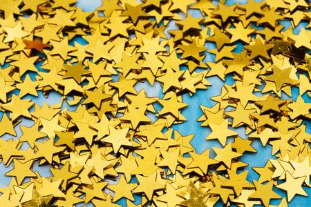 star border: Close up of shiny gold stars on blue background, gold star background Stock Photo