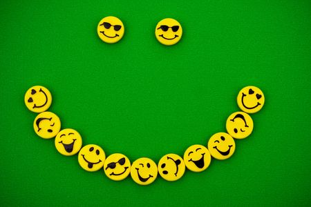 green background: Smile made of multiple smiley faces on green background, smiley faces