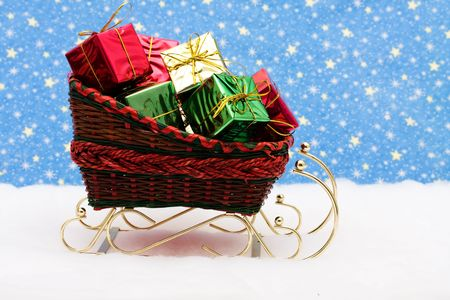 filled: Red and Green wicker sleigh filled with presents on snow with star background, Santas Sleigh Stock Photo