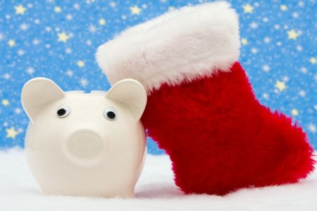 christmas savings: Piggy bank and red stocking sitting on snow with star background, Christmas savings