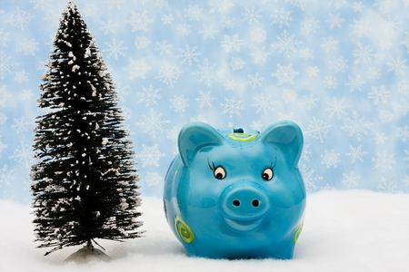 christmas savings: Piggy bank and tree on snow with snowflake background, Christmas savings