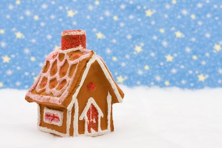 Ontbijtkoek huis op sneeuw met ster achtergrond, peperkoek huis