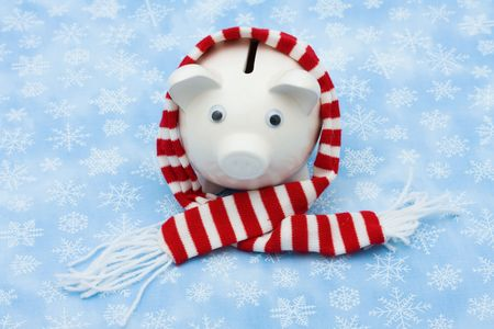 christmas savings: Piggy bank wearing a scarf on snowflake background, Christmas savings
