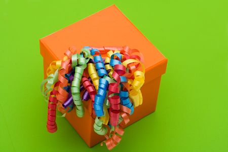 Orange gift with ribbons on green background with copy space, colourful gift photo