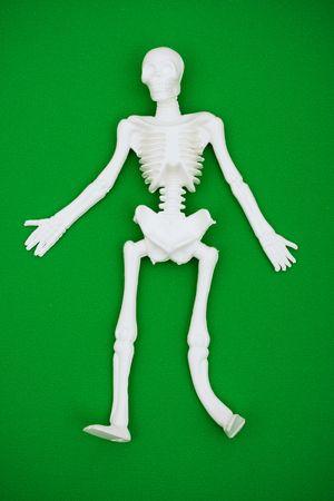 horrify: White skeleton on green background with copy space, skeleton