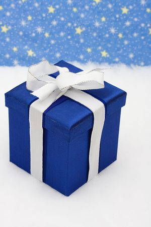 Blue present wrapped with white bow on snow with star background, holiday present