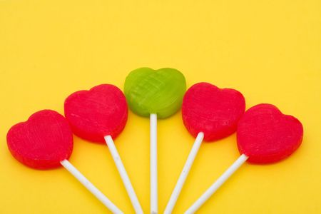 lolli: Red and green heart shaped lollipops on yellow background, heart lollipops