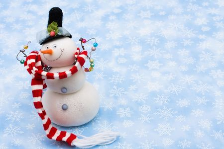 Snowman wearing scarf on blue snowflake background, merry Christmas  photo