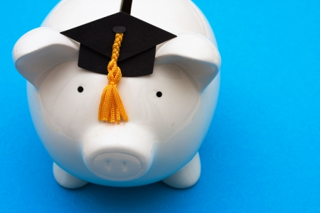 Piggy bank with graduation cap on blue background, saving for college