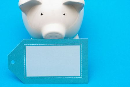 Piggy bank with blank tag on blue background with copy space, savings interest rate photo