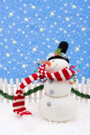 picket fence: Snowman and white picket fence with green garland and red bow, merry Christmas
