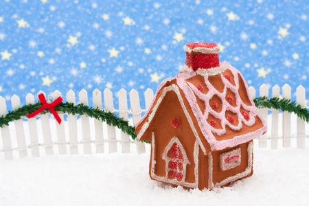 picket fence: Gingerbread house and white picket fence with green garland and red bow, merry Christmas