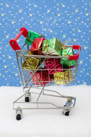 shopping buggy: Shopping cart filled with presents on snow with star background, Christmas shopping Stock Photo