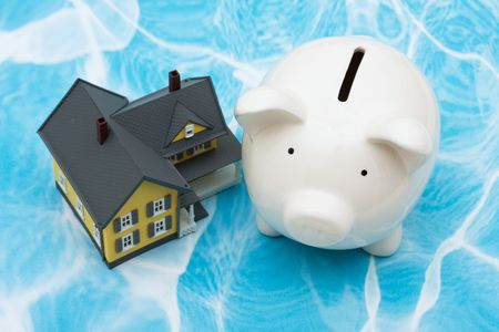 Model house with piggy bank on blue background. home finances