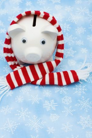 Piggy bank wearing a scarf on snowflake background, Christmas savings