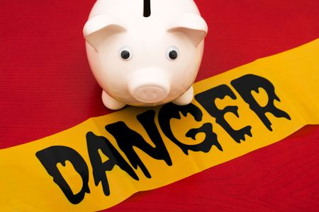 danger: Pink piggy bank with danger tape on red background, dangerous investments
