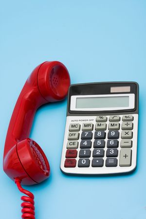 financial questions:  Telephone with calculator – help with your financial questions Stock Photo