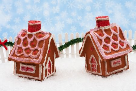 picket green: Two gingerbread houses and white picket fence with green garland and red bow, merry Christmas