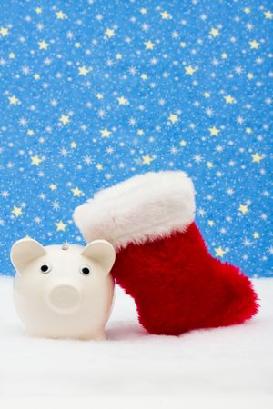 christmas savings: Piggy bank and red stocking sitting on snow with star , Christmas savings