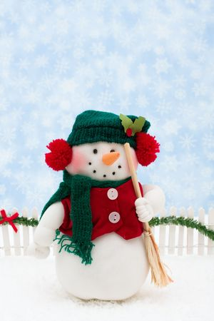 Snowman and white picket fence with green garland and red bow, merry Christmas photo