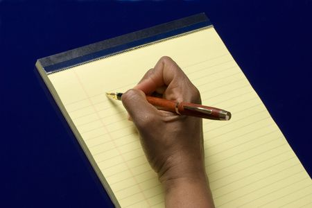 Hand with pen in it writing on yellow notepad on blue background, taking notes photo