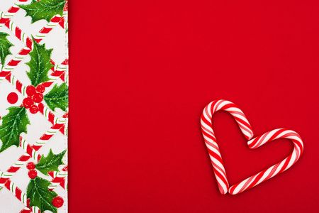 Candy cane, holly berries and leaf border on red background, Christmas border photo
